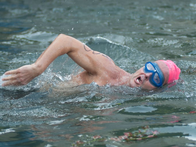 A swimmer turns up for air during the Tri-Indy Triathlon, Sunday, Aug. 3, 2014 in the Indiana Central Canal. The triathlon route was centered at White River State Park and went as far north as the Major Taylor Velodrome.
