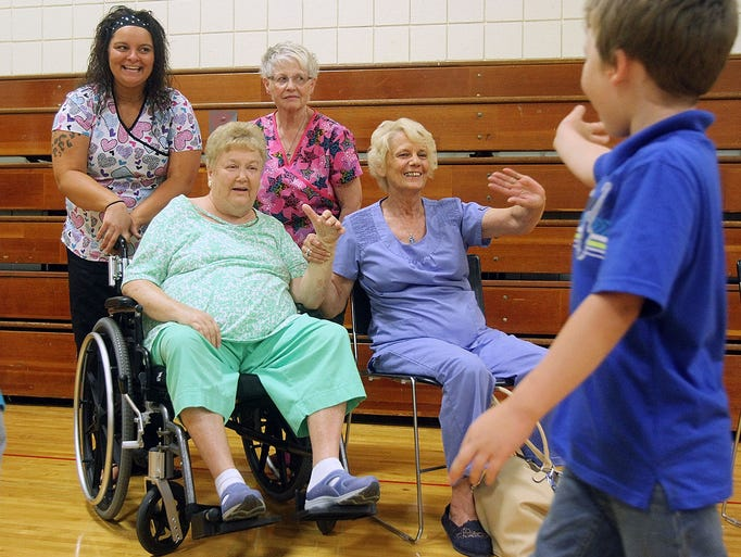 Janis Dodds (left) gets a hand waving to students from caregiver Kathy Foreman as kids leave the gymnasium an Ice Bucket Challenge assembly at George Washington Elementary School on Friday, Aug. 22, 2014. Dodd, a retired Marion City School teacher, and was diagnosed with Lou Gehrig's disease about a year ago.