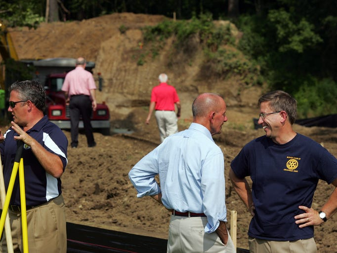 Past Granville Rotary President Dr. John Weigand, right, speaks with Granville Township Trustee Bill Mason after a ground breaking ceremony held at Raccoon Valley Park for a new bridge connecting the park to the bike path by crossing Raccoon Creek.