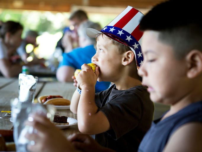 Casey Liess, left, and Joshua Bravo enjoy a picnic for Fresh Air families at Elks Lodge in Henrietta on July 5, 2014. Liess' family is hosting Bravo from Brooklyn as part of the Fresh Air Fund, a program which allows children from New York City to experience non-urban life.