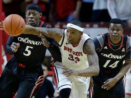 Rutgers forward Wally Judge (33) grabs for the ball in front of Cincinnati  forward Justin Jackson (5) and guard Ge'Lawn Guyn (14) during the first half of an NCAA college basketball game Saturday, March 8, 2014, in Piscataway, N.J. (AP Photo/Mel Evans)