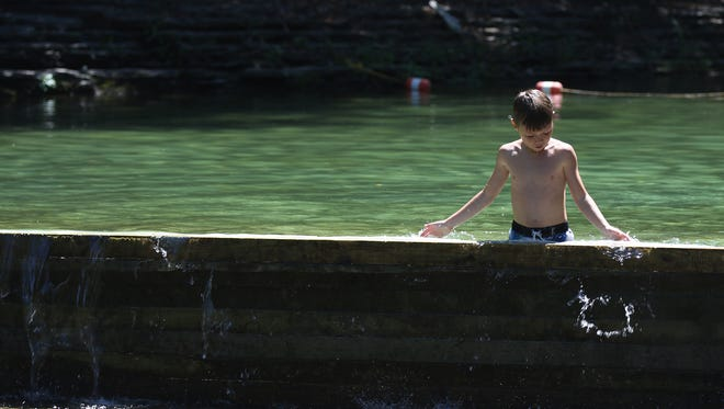 Malakai Kreamer, 8, of Cuba, New York plays with the water in the two foot wading area at Stony Brook State Park in Dansville on Aug. 8, 2016.