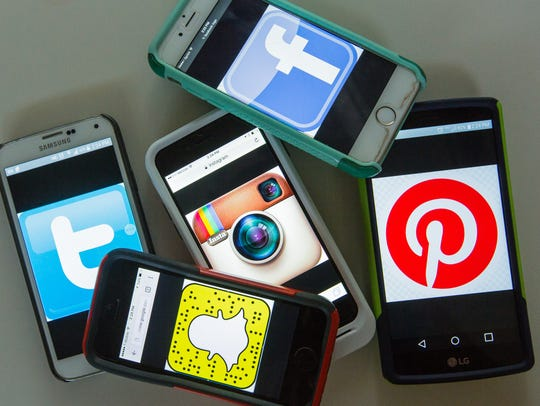 Pictured are cellphones with social media graphics