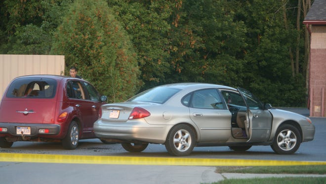 Two cars whose drivers were involved in a shooting sit in the driveway of a car wash in Ionia, Mich., on Wednesday.