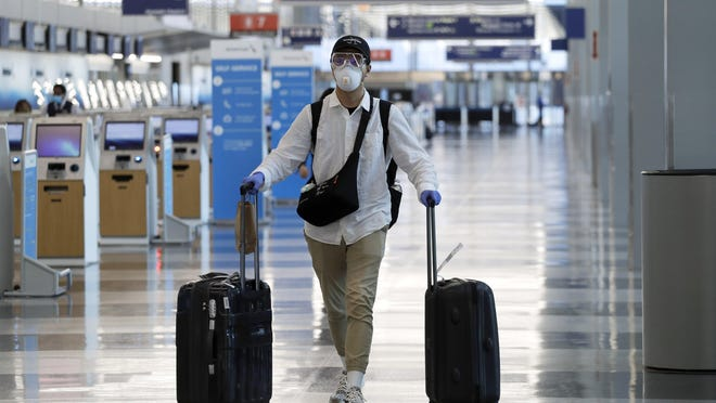 A traveler wears a mask and protective goggles as he walks through Terminal 3 at O'Hare International Airport Tuesday, June 16, 2020, in Chicago.