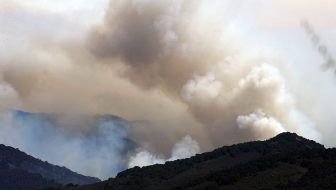 Smoke from both controlled burns and the Soberanes Fire billows high in the mountains behind E. Carmel Valley Road on Sunday, August 7th, 2016.