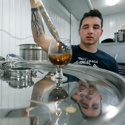 Jared Mesiti takes a sample from a beer fermenter to