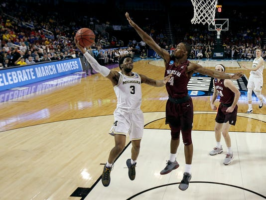 Michigan guard Zavier Simpson (3) gets past Montana guard Sayeed Pridgett (4) for a shot during the second half of an NCAA men's college basketball tournament first-round game Thursday, March 15, 2018, in Wichita, Kan. Michigan won 61-47. (AP Photo/Charlie Riedel)