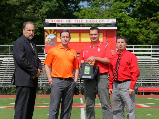 (second from left) Joey Bombara, EMR, certified AED specialist for Cardiac Science, a leading manufacturer of AEDs, presents an AED to (left) Charles Ross, principal, (third from left) Tim Root, athletic trainer who saved the life of a Colonia High School basketball player who went into cardiac arrest earlier this year, and (right) Jeff DiCocco, director of athletics, at Edison High School in Edison, NJ Friday June 17, 2016. Edison has been a leader in student-athlete afety ever since one of its former football stars, Kittim Sherrrod, collapsed and died during a track practice several years ago.