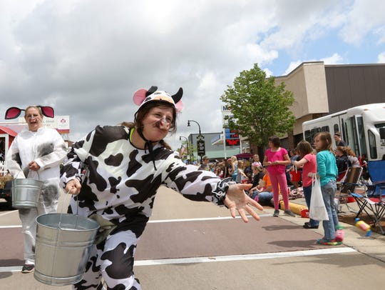 Frances Skora, dressed as a cow, throws candy to children