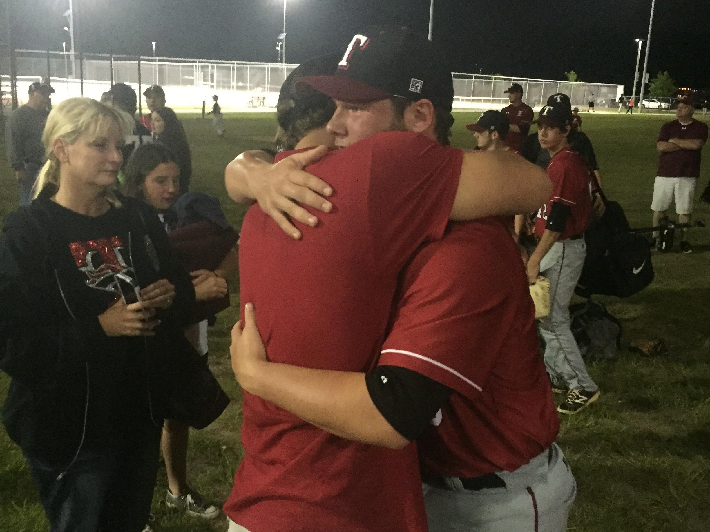 Tate catcher Cole Halfacre (right) embraces Everett Lockman, a Tate baseball alumi (C/O 2009) after a hard loss in the Region 1-7A Finals to St. John's Creekside.