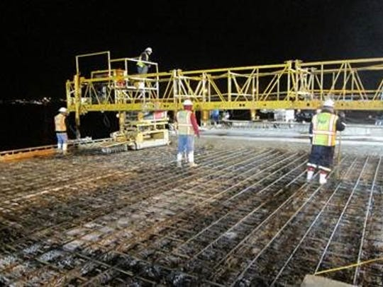 Overnight construction crew pouring new concrete deck,