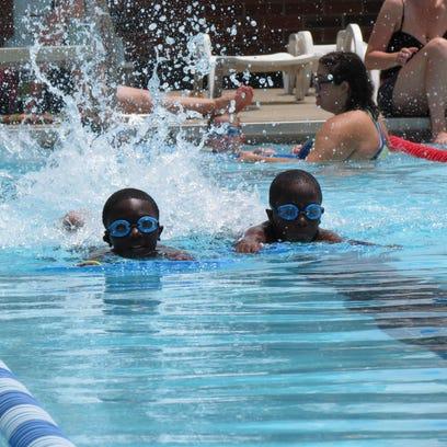 Stephen Ellison, left, and Caleb Ellison, right, swim