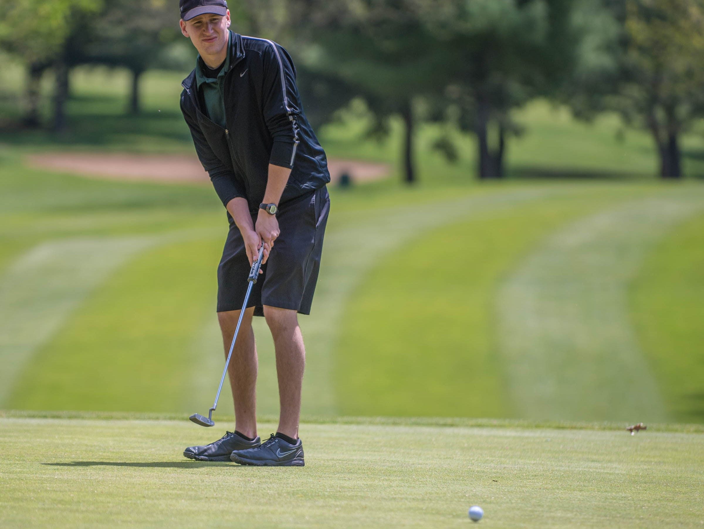 Pennfield senior Chase Williamson hits his putt during All City High School Golf at Riverside Golf Club on Friday.