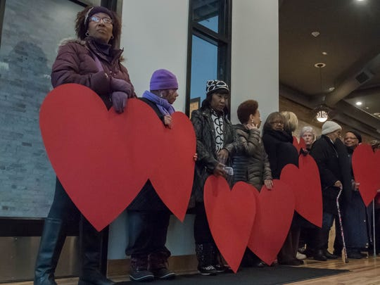 Participants gather with large heart cut outs at the
