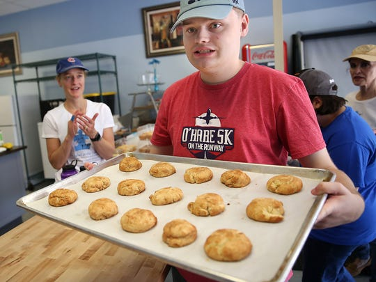 Jacob Wittman shows a tray of Snickerdoodles, as his mom Shelly Henley, left, applauds, on No Label at the Table's baking day, in Fishers, Friday, June 9, 2017.   No Label at the Table is a gluten/dairy-free food company whose mission is to give employment opportunities to people on the autism spectrum.  They also give job skills training to those employees.  Shelly Henley started the company with her son Jacob Wittman, who is on the spectrum.