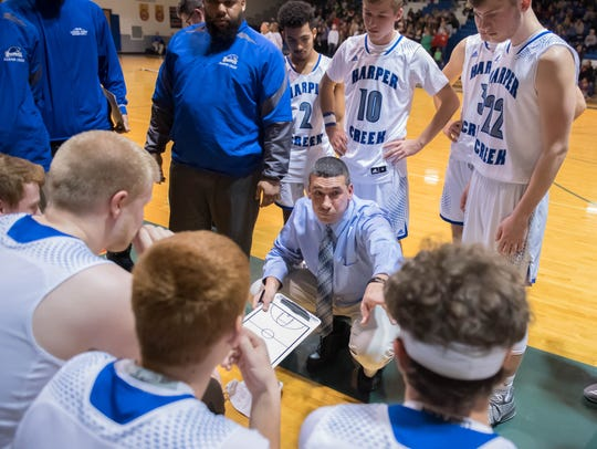 Harper Creek's head coach Matt Bowling talks to his