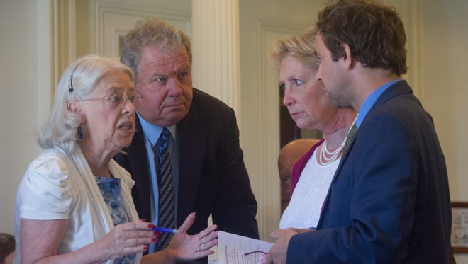 Senators including Peg Flory, R-Rutland, from left, David Soucy, R-Rutland, Carolyn Branagan, R-Franklin and President Pro Tempore Tim Ashe, D/P-Chittenden, huddle in advance of a budget and tax bill vote on Thursday at the Statehouse in Montpelier.
