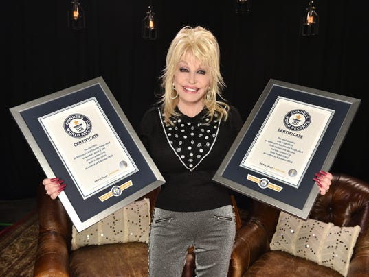 Dolly Parton with her two Guinness World Records plaques in hand