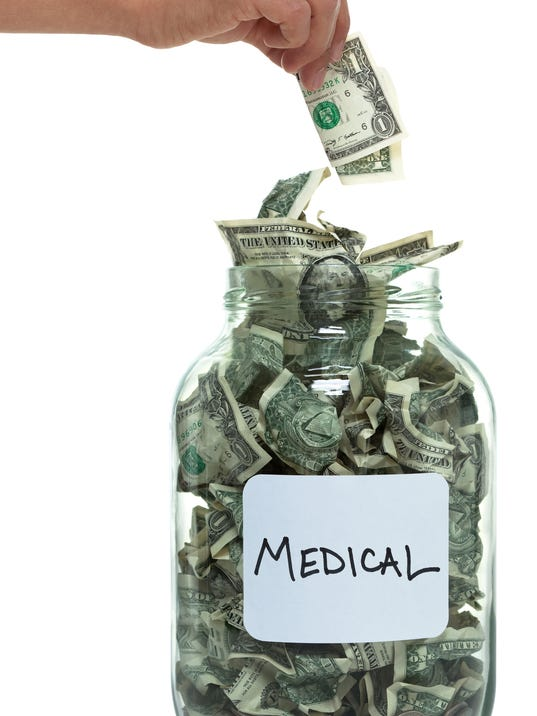 Hand putting money into savings jar with white medical label