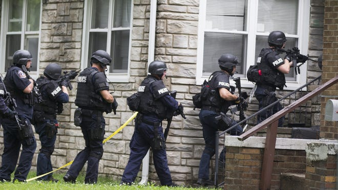 SWAT officers from the Indianapolis Metropolitan Police Department investigate the scene of a June 11 shooting on the Eastside.
