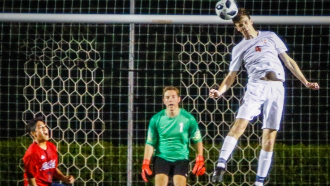 Blackman defender J.C. Conn heads a ball as Blaze goalkeeper Colin Dunkley watches in the background during Tuesday's match.