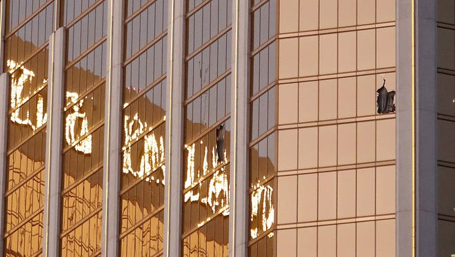 Broken windows are seen on a high floor in the Mandalay Bay hotel facing the scene of the mass shooting at the Route 91 Harvest festival in Las Vegas on Monday.