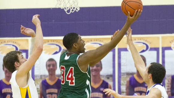 Lawrence North High School freshman Kevin Easley, Jr. (34) tries to get a put-back basket after grabbing a rebound during first half action. Guerin Catholic High School hosted Lawrence North High School in boys varsity basketball, Friday, Dec. 19, 2014.