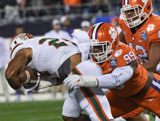 Clemson defensive end Clelin Ferrell (99) tackles Miami running back Travis Homer (24) during the first quarter of the Dr.Pepper ACC football championship in Charlotte in December.