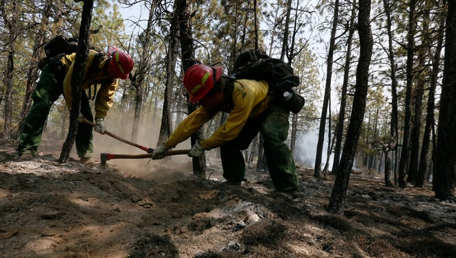 Firefighters Ron Huffman, left, and Ivan Harmon rake out hot spots, Sunday, June 8, 2014 in the scorched ground near an area that investigators were searching for the cause of the Two Bulls Fire west of Bend, Ore. (AP Photo/The Bulletin, Joe Kline)