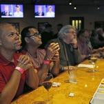 Riccardo Bailey, left, of Miami Beach, Fla., and Burhan Ahmed, of Wilton Manors, Fla., watch the presidential debate on television at Bokampers Sports Bar & Grill, Wednesday, Oct. 19, 2016, in Miramar, Fla. (AP Photo/Wilfredo Lee)