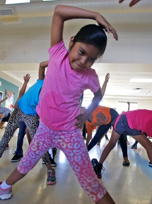 Carla Joe, center, stretches after a run on Thursday during the annual Wings of America's Running and Fitness Camp at Ojo Amarillo Elementary School.