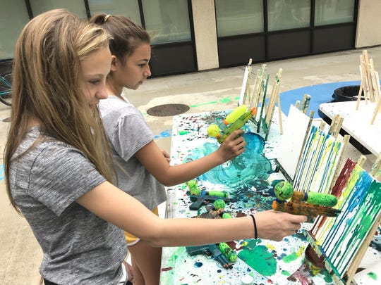Redding sixth-graders Vanessa Tilcock, left, and Izzy Garcia create squirt-gun art at Saturday's Minds Matter Resource Fair at the Market Street Promenade.