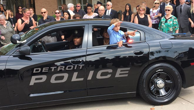 Alexander Steil, 3, salutes out the window of a police car in the funeral procession Sept. 23, 2016, for his father, Detroit Police Sgt. Kenneth Steil. Police Chief James Craig promoted Steil to captain at the funeral at St. Joan of Arc Catholic Church.