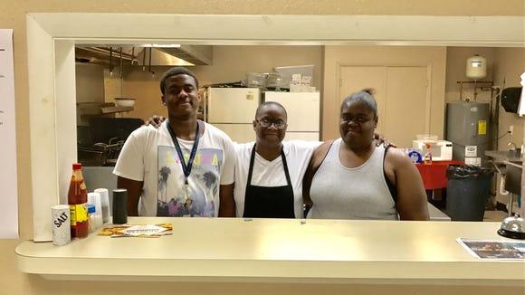 Vashawn Williams, center, runs Taste of Love BBQ with her son, Xavier Cooper, and wife,  Schamona Joiner.