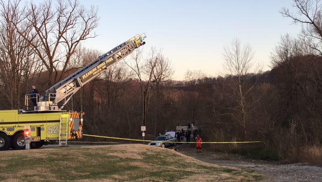 A fire truck ladder is lowered as officials prepare to extract a body from a creek near Woodridge Lake Boulevard on Monday