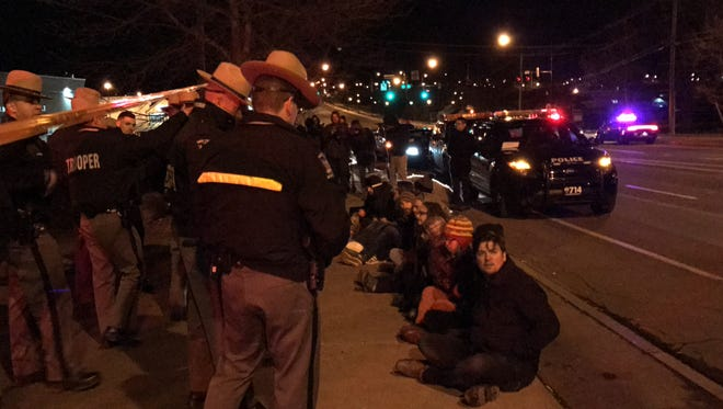 Protesters attempt to block vehicles from leaving a border patrol station in Irondequoit.