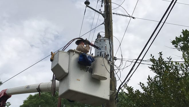 A Mississippi Power employee works to restore electricity to the Parkhaven neighborhood of Hattiesburg after a tree tore down a few power lines in the area.