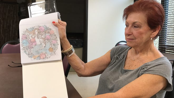 Judy Tucker, 75, shows off the mermaid coloring page she is working on at Bayview Senior Citizens Center.