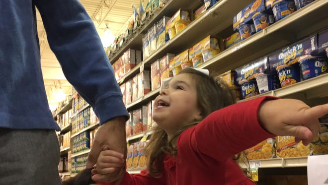 Susana Resende tells her father, Bruno, where she wants to go next at Renfroe's Market on East Chase Parkway. The 4-year-old had her birthday party at the market on Sunday, Dec. 10, 2017, as a way to buy for families in need.