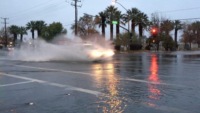 FILE - A vehicle passes through the flooded intersection of Farrell Drive and Ramon Road in Palm Springs.