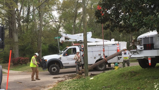 Hattiesburg police and fire department officers work to clear Edwards Street at County Drive where an 18-wheeler hit a power pole. Mississippi Power lineman had to replace the downed pole.