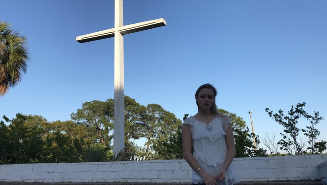 Serena Schwerdfeger sings Sunday, April 15, 2018, at the Bayview Park cross in Pensacola.