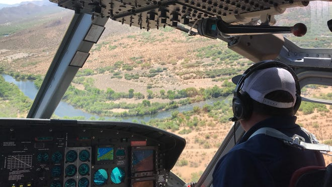 SRP chief helicopter pilot Rob Ackerman navigates over a section of the Salt River northeast of Mesa on May 9, 2018.