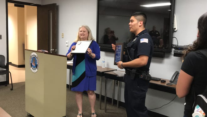 """Wisconsin Rapids Citizens Police Academy Alumni President Margo Dakins awards  Rapids Officer German Olivares the 2018 """"Officer of the Year"""" plaque and certificate."""