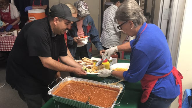 Fausto Nungarai, left, of Oxnard, gets a serving of hot dogs and beans at the Many Meals of Camarillo program at St. Mary Magdalen Church on Monday.