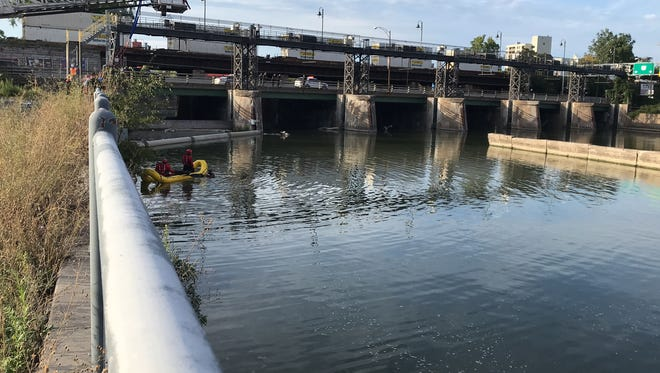 Two firefighters and two police scuba divers move toward a body in the Genesee River Thursday.