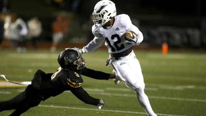 Georgia Southern running back Wesley Kennedy III (12) of Savannah gets pressure from Appalachian State defensive back Shaun Jolly (3) during a game Oct. 31, 2019, in Boone, NC. The Sun Belt Conference announced Tuesday that teams will play eight conference games in 2020.