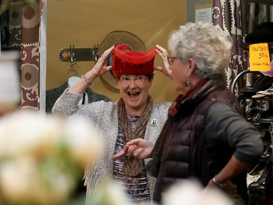 Debbie Littlejohn, 66, tries on a fancy red hat Tuesday while browsing the Thrift Shop with friend Linda Heys, 71, at the Waterfront Park Community Center.