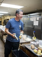 Joe Scully, owner of Chestnut, peels potatoes to make chips while talking with an employee Thursday May 18, 2017 in the catering kitchen of Chestnut, a restaurant located in Biltmore Avenue.